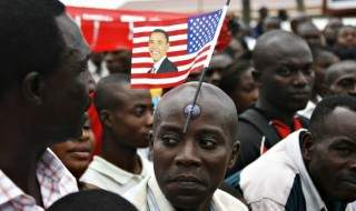 A man with a flag stuck to his forehead waits to catch a glimpse of U.S. President Barack Obama in Accra