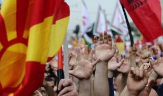 Protesters waving Macedonian and Albanian flags raise their hands during an anti-government demonstration in Skopje