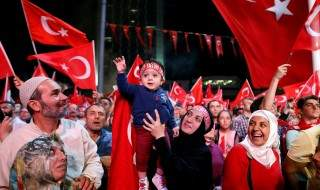 A woman raises a boy in the air during a pro-government demonstration supporting Turkish President Tayyip Erdogan, at Taksim square in central Istanbul, Turkey, July 19, 2016.REUTERS/Ammar Awad